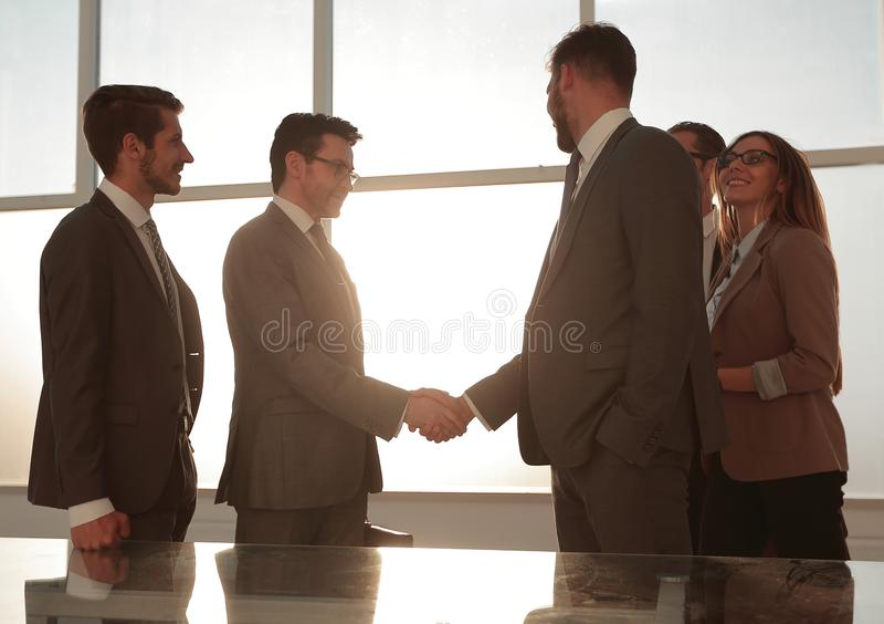 Partners som har en affärsdiskussion i ett soligt kontor royaltyfri bild