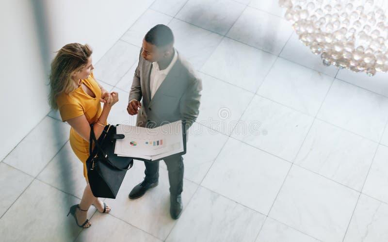 Partners som revieving ett affärsdokument i lobby royaltyfria bilder