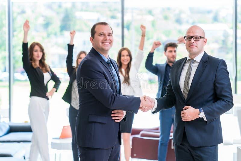 Partnershandenschudden na het ondertekenen van contract stock foto's