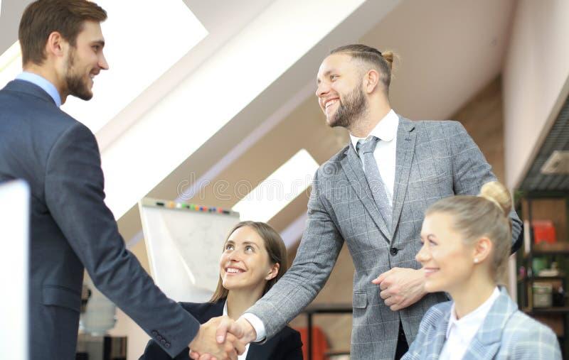 Partnershandenschudden over bedrijfsvoorwerpen op werkplaats stock afbeelding