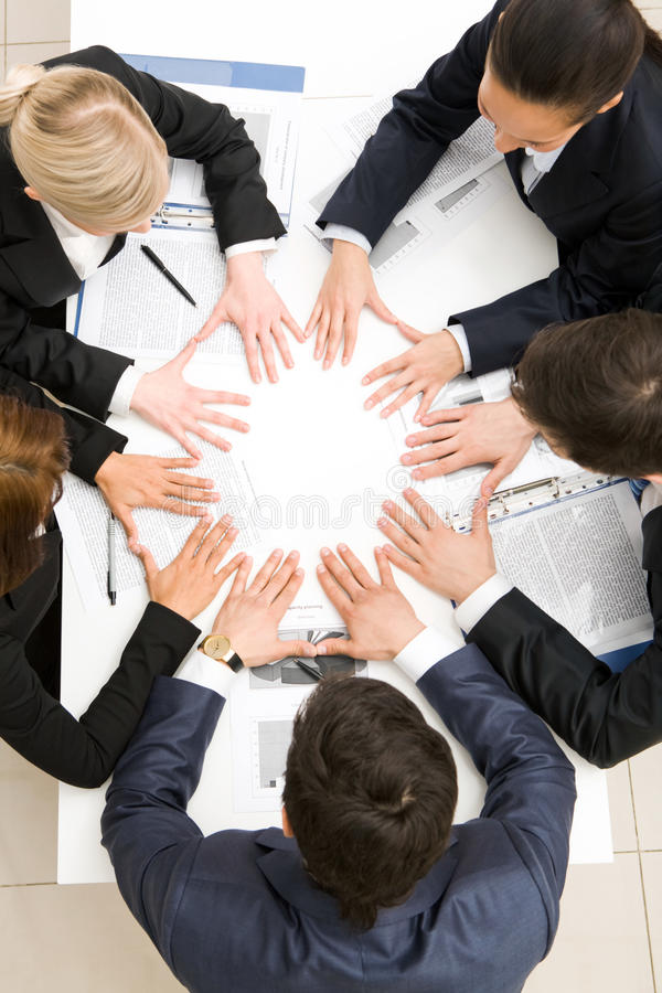 Partnership. Above view of business partners making circle from hands on table royalty free stock image