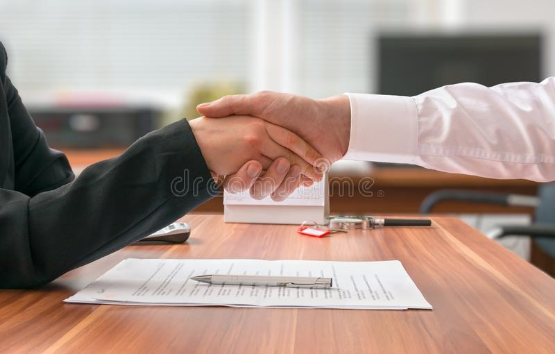 Partnership concept. Businessman and woman sitting behind desk with agreement royalty free stock image