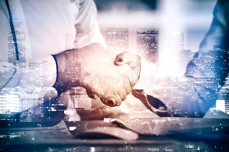 Partnership concept. Close up of handshake on night city background. Partnership concept. Double exposure royalty free stock images