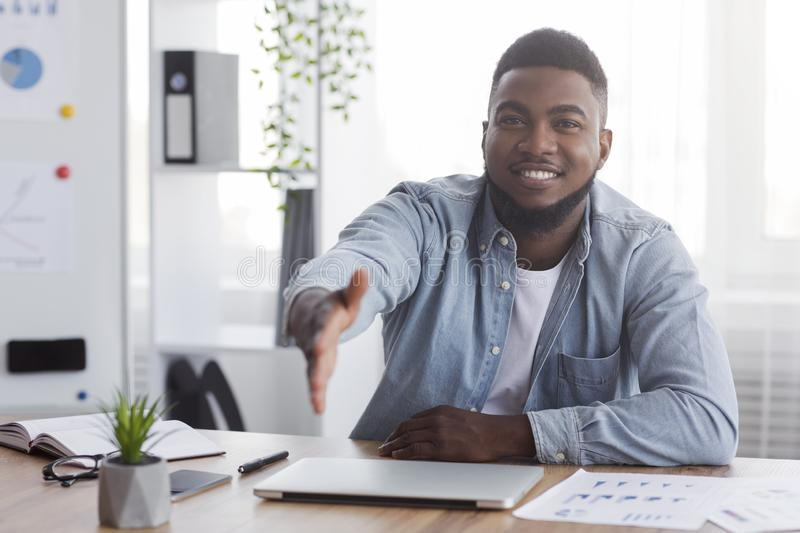 Handsome Black Manager Extending hand for handshake after successful deal. Partnership concept. Handsome African American Manager Extending hand for handshake royalty free stock photo