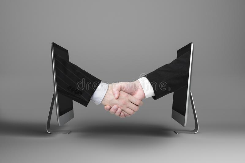 Partnership and digital business concept. Businessmen shaking hands through computer screens on grey background with shadow. Partnership and digital business stock photo