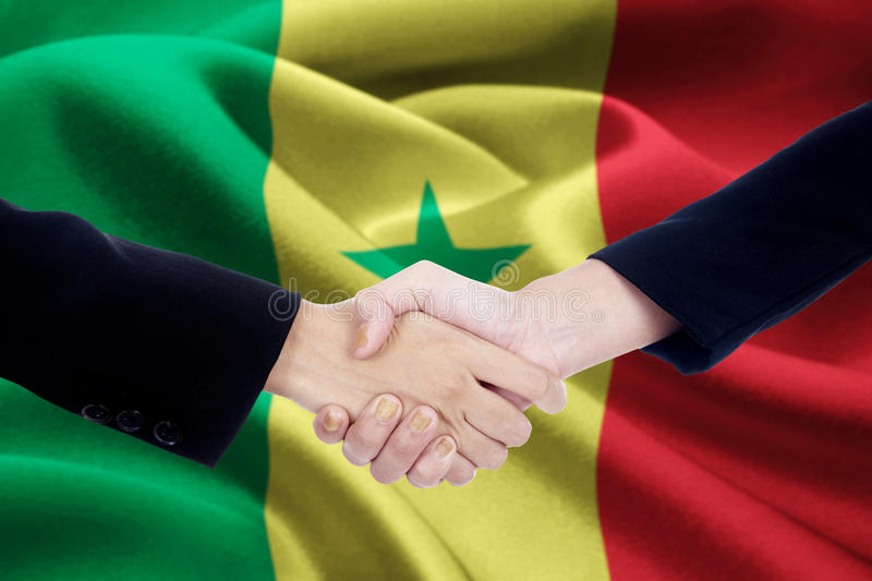 Partnership handshake with flag of Senegal. Photo of partnership handshake with two businesspeople hands, closing a meeting and shaking hands with a Senegal flag stock photos