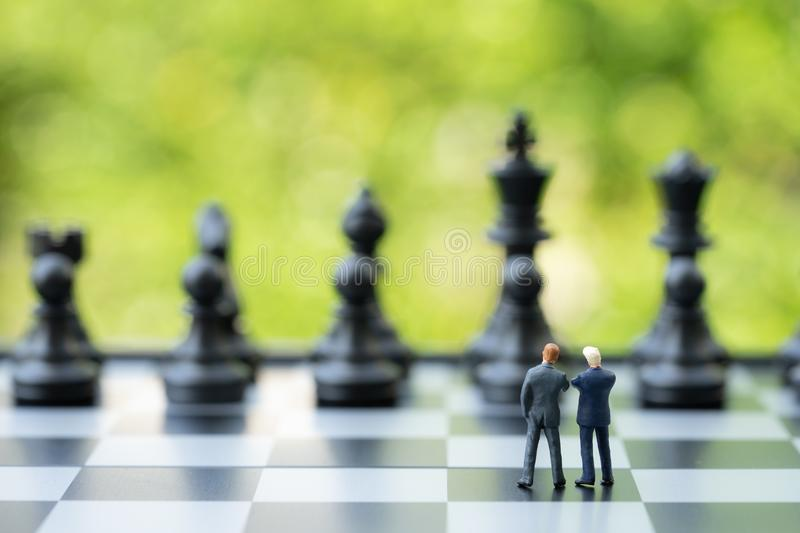 Partnership and teamwork in business strategy concept, two miniature people businessmen work as team, standing on chessboard look stock images