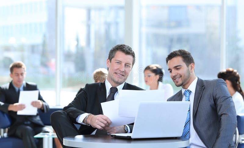 Partnery biznesowi siedzi w lobby bank dyskutują pieniężnych zagadnienia obrazy royalty free