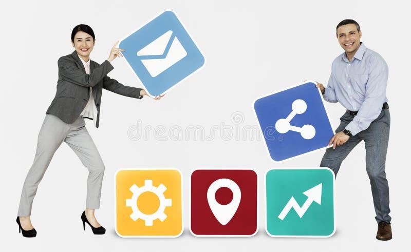 Partnery biznesowi trzyma online ikony zdjęcia royalty free