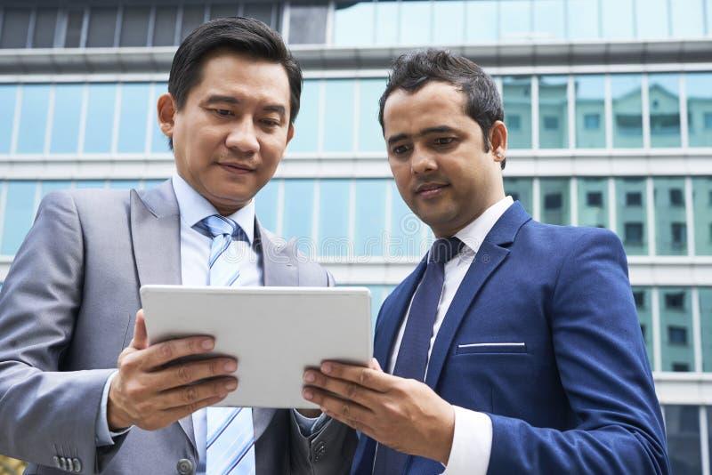 Partnery biznesowi używa pastylka komputer osobistego zdjęcie stock
