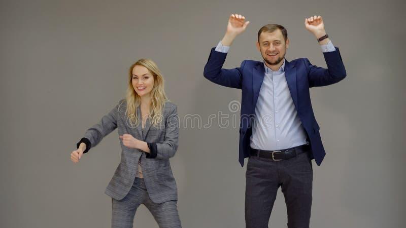 Partnery biznesowi zaznacza pomyślną transakcję na odosobnionym popielatym tle tanczą, zdjęcia royalty free