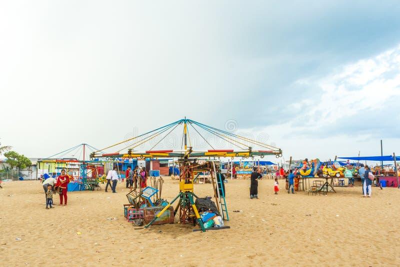 Partouzeur en bois d'isolement de tour de cheval pour les enfants avec le ciel bleu, nuages foncés à l'arrière-plan, plage de mar photos stock
