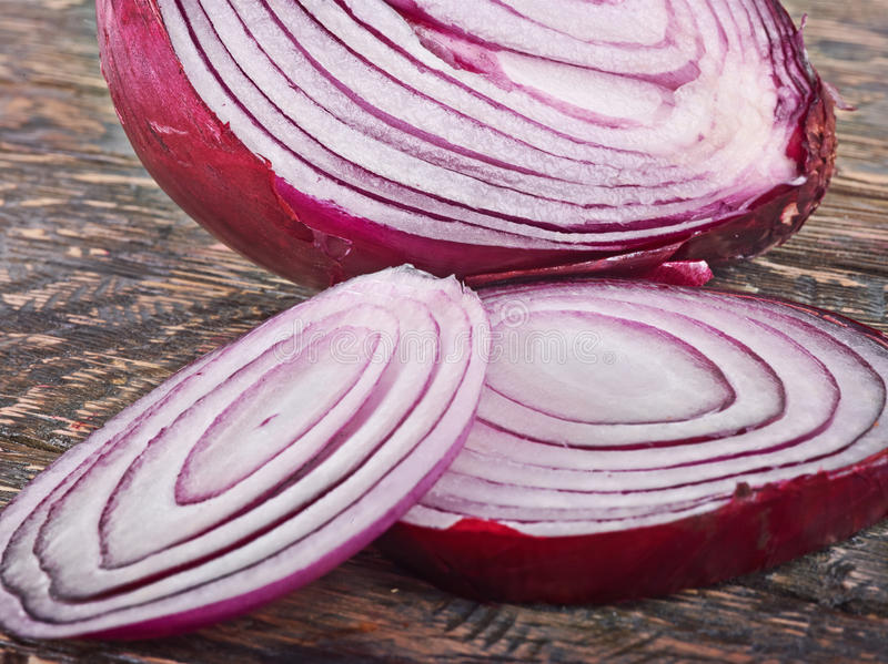 Parts of cut purple onion. Cut purple onion parts with outstanding texture on wooden background stock photography