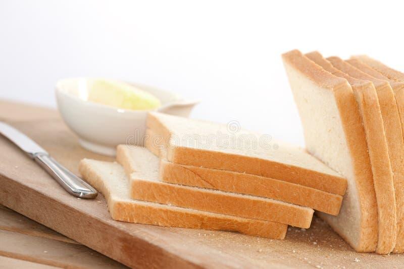 Parts de pain avec le bol de beurre image libre de droits