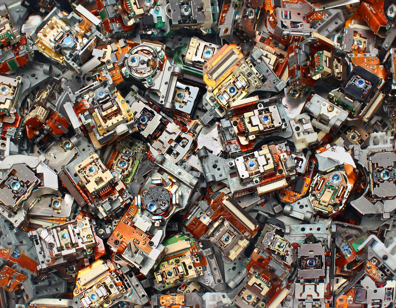 Parts of old optical drives as industrial waste background. Broken cd and dvd laser pickup units, obsolete technology concept image stock image