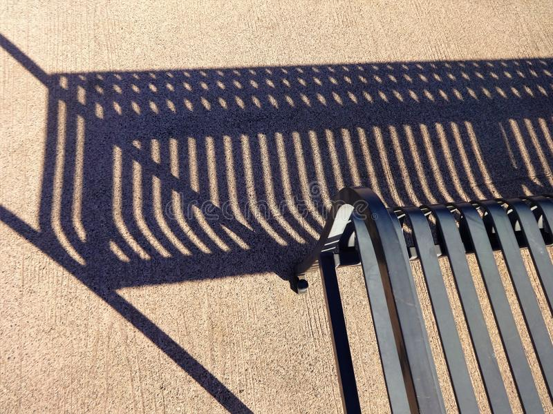 The parts of steel bench and shadow on a pavement. Graphic image of steel bench, shadow and a pavement royalty free stock images