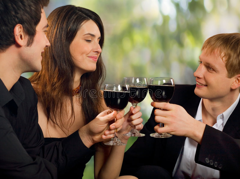 At party. Two young happy smiling men flirting with attractive woman with red-wine, at celebration or party