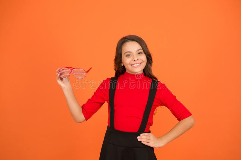 Party accessory. Having fun. Carnival party. Masquerade concept. Kid wear eyeglasses. Eyewear fashion store. Girl with. Eyeglasses orange background. Event and stock photo