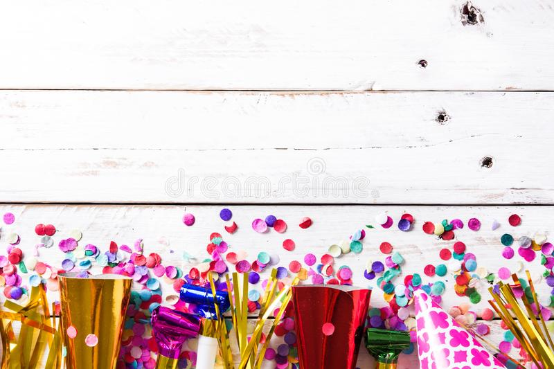 Party background. Party caps and confetti on white wooden background. stock photo