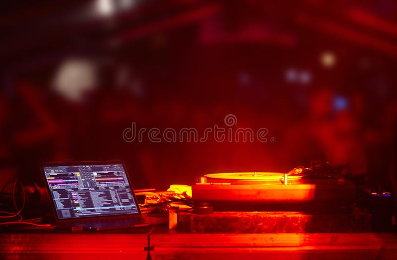 Party backstage, dj booth equipment turntables computer, out of focus blured crowd royalty free stock photo
