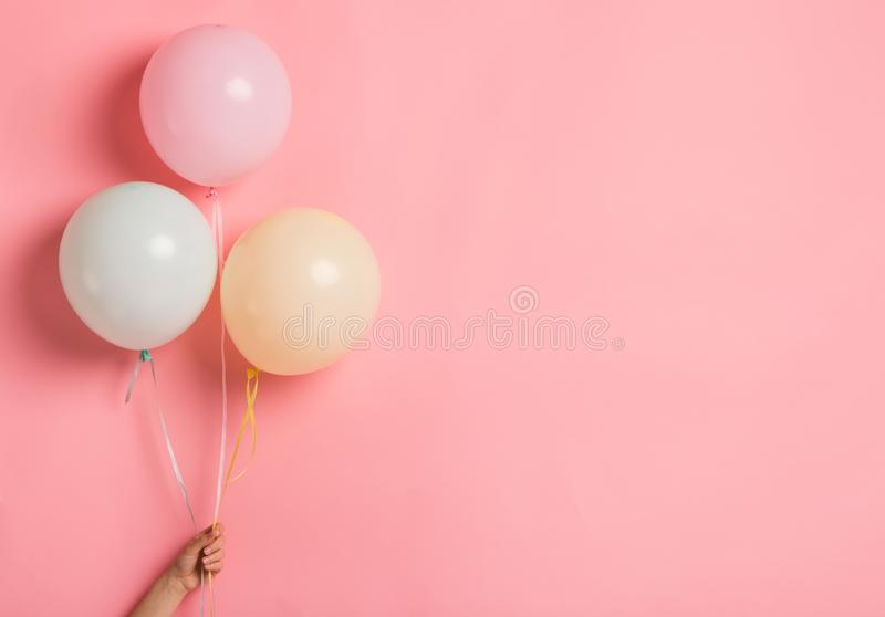 Party balloon bunch in woman hand on pink background royalty free stock images