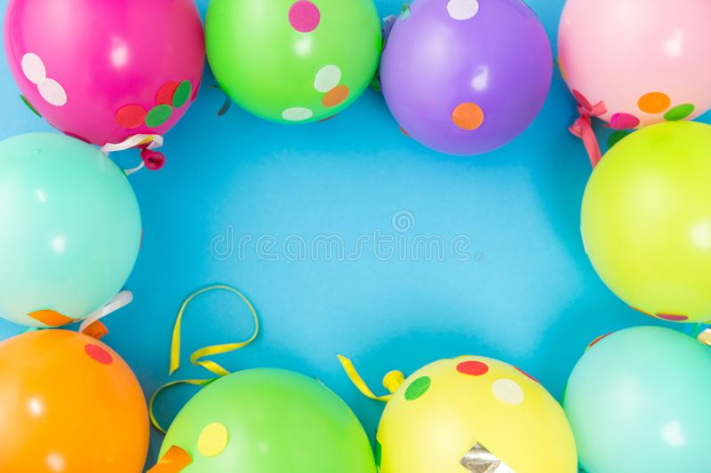 Party balloons and confetti on blue background. Party props, celebration and decoration concept - colorful balloons and confetti on blue background stock image