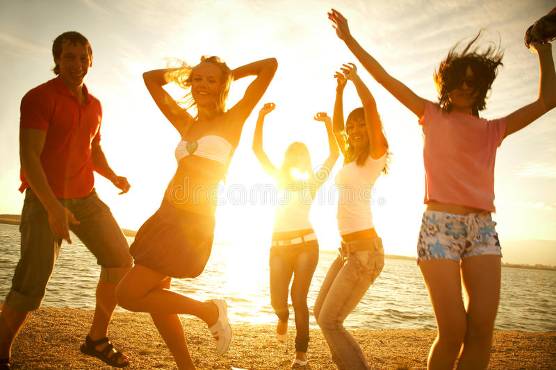 Party on the beach. Happy young teens dancing at the beach on beautiful summer sunset