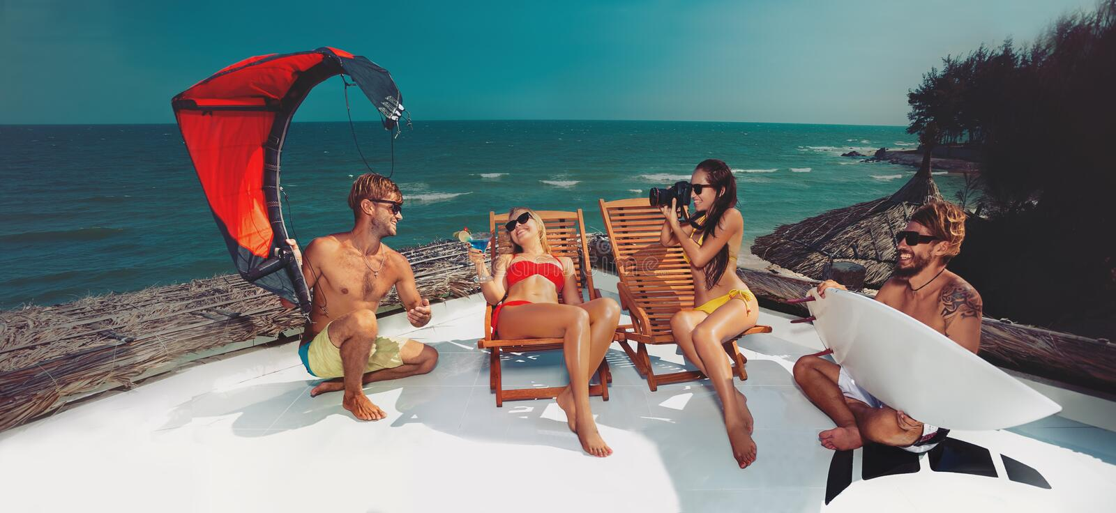 Party on beach. Surfer and kiter boys with beautiful girls group stay on beach royalty free stock photo