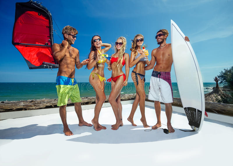 Party on beach. Surfer and kiter boys with beautiful girls group stay on beach stock images