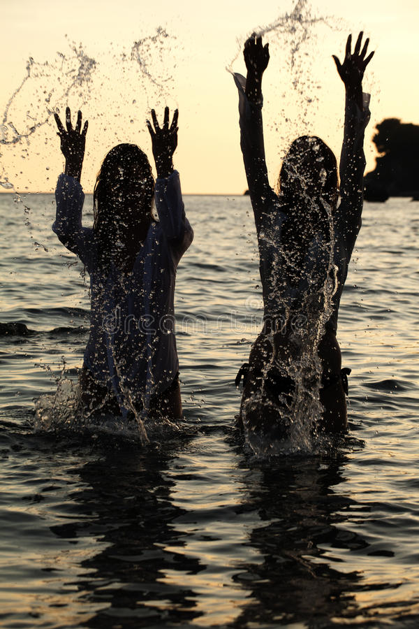 Party on beach. Two Woman dancing and spraying at the beach on beautiful summer sunset royalty free stock photography