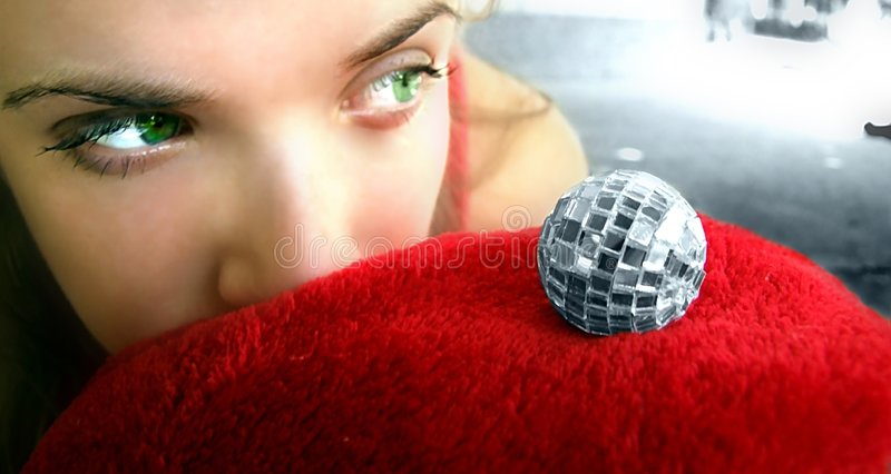 Party beauty. An attractive young woman looking at a disco ball royalty free stock photography