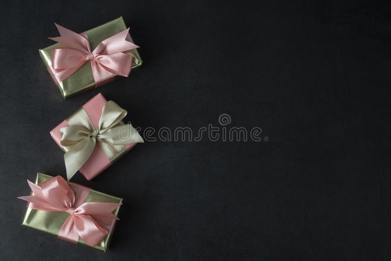Party, birthday present in golden box with pink bow on black background. Top view or flat lay. Copy space stock image
