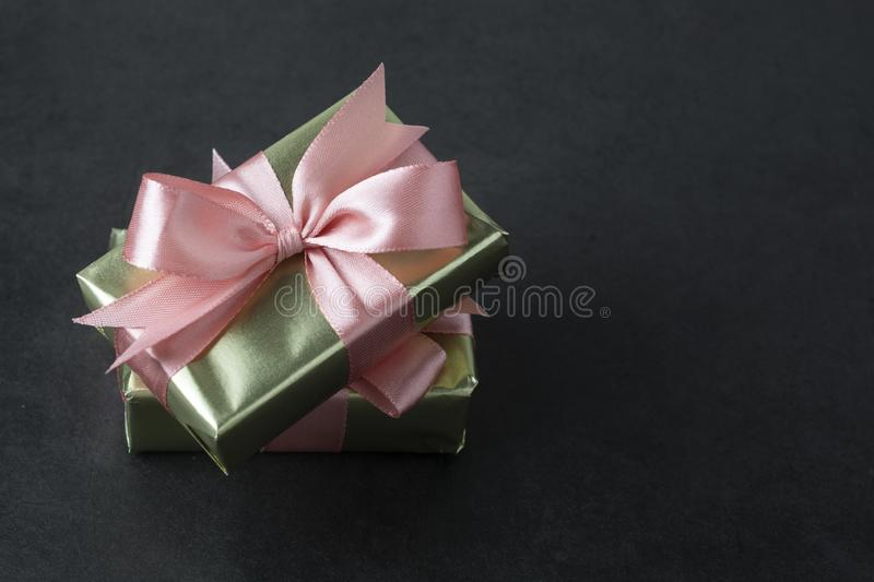 Party, birthday present in golden box with pink bow on black background. Top view or flat lay. Copy space stock photos