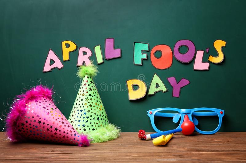 Party caps, glasses and horns. On table near chalkboard with phrase `April fool`s day stock photo