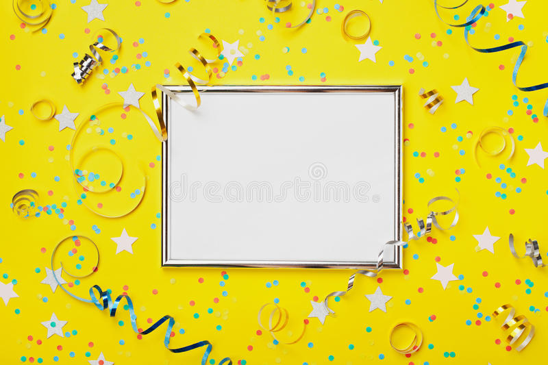 Party, carnival or birthday background decorated silver frame with colorful confetti and streamer on yellow table top view. Flat lay style. Holiday mockup royalty free stock images