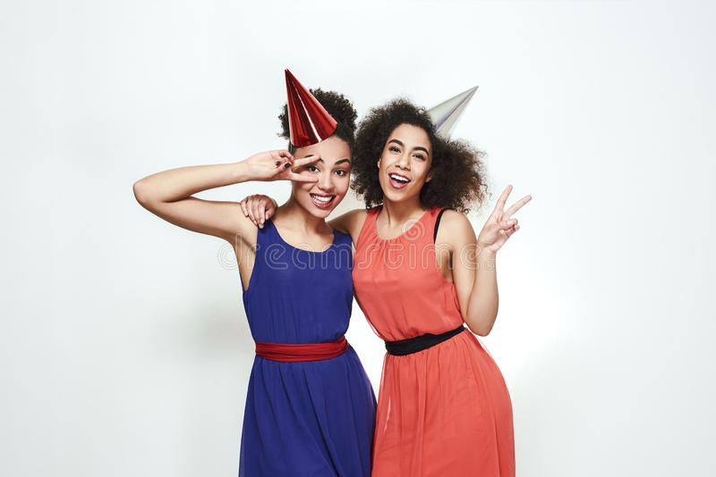 Party celebration. Portrait of two positive and young afro american women in beautiful evening dresses and party hats royalty free stock image