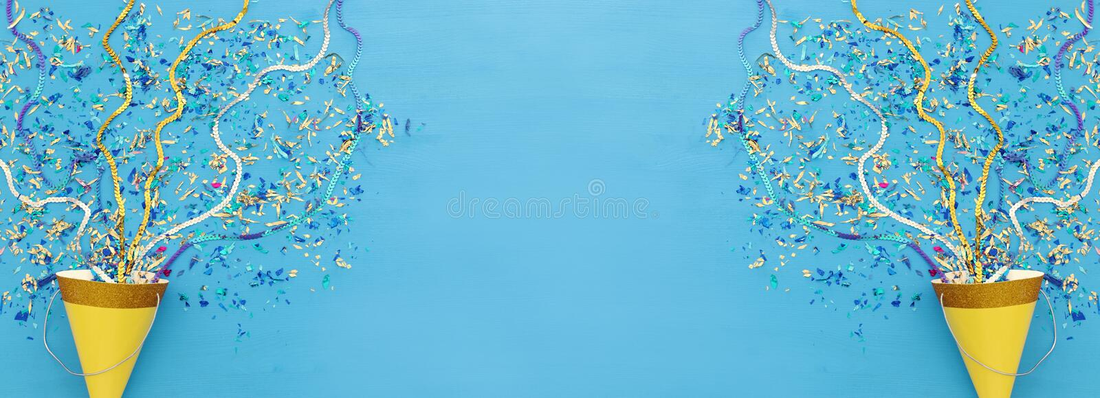 Party colorful confetti and clown hat over blue wooden background . Top view, flat lay. royalty free stock photo