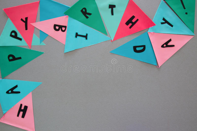 Party colorful flags on grey table with worlds HAPPY BIRTHDAY stock photography