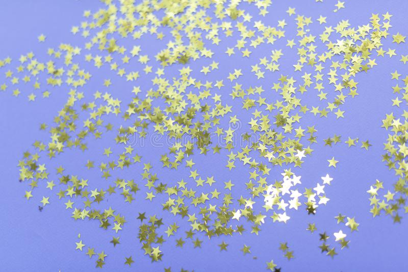 Party composition. Golden stars decorations on purple background. Christmas, winter, new year, birtda concept. Selective. Focus, top view, copy space royalty free stock photo