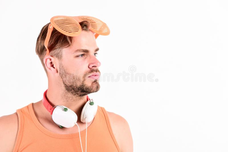 Party concept. Dj boy. Popular summer track list. Technology and entertainment. Modern life. Summer music chart. Handsome man with headphones and sunglasses royalty free stock images