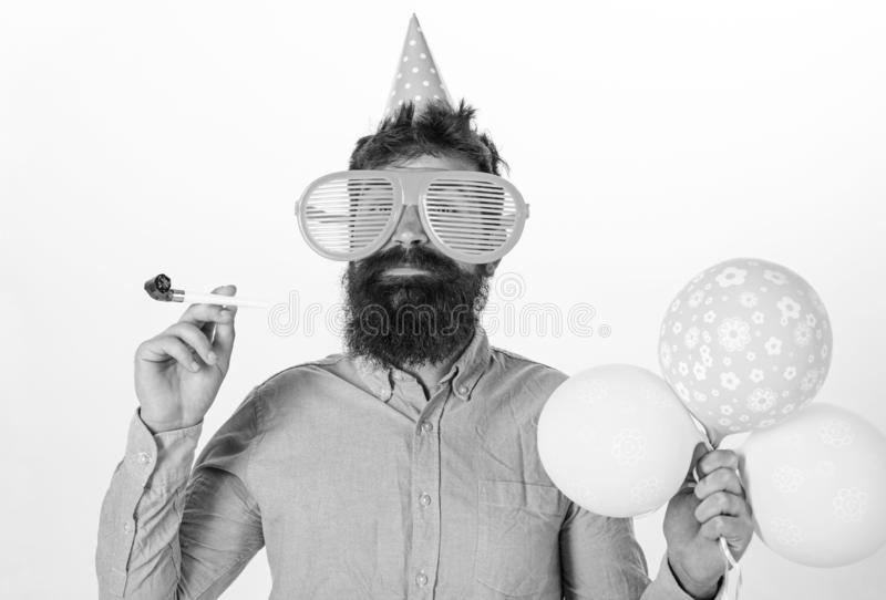 Party concept. Hipster in giant sunglasses celebrating birthday. Guy in party hat with party horn celebrates. Man with. Beard and mustache on happy face holds stock images
