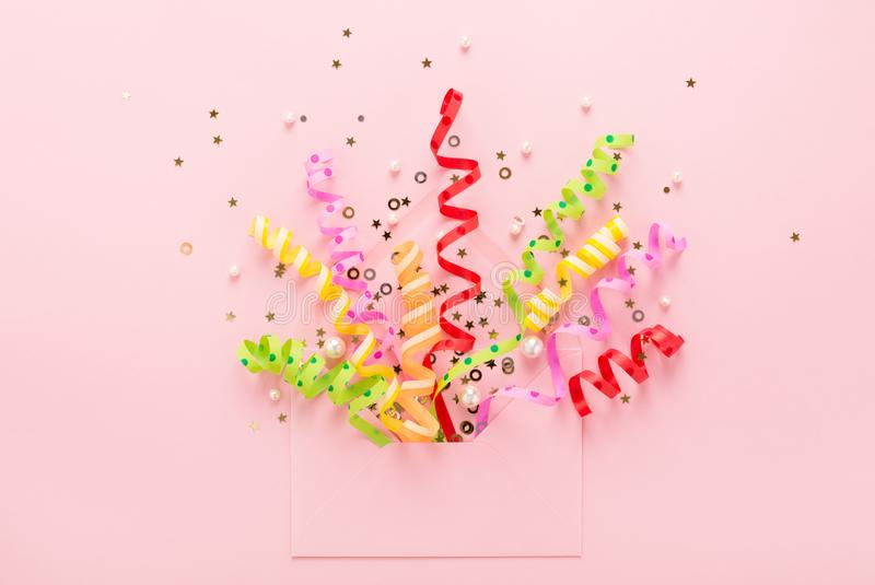 Party confetti & sequins explosion from envelope on pink. Confetti & sequins explosion. Opened envelope with festive streamers on pink background. Party royalty free stock photography