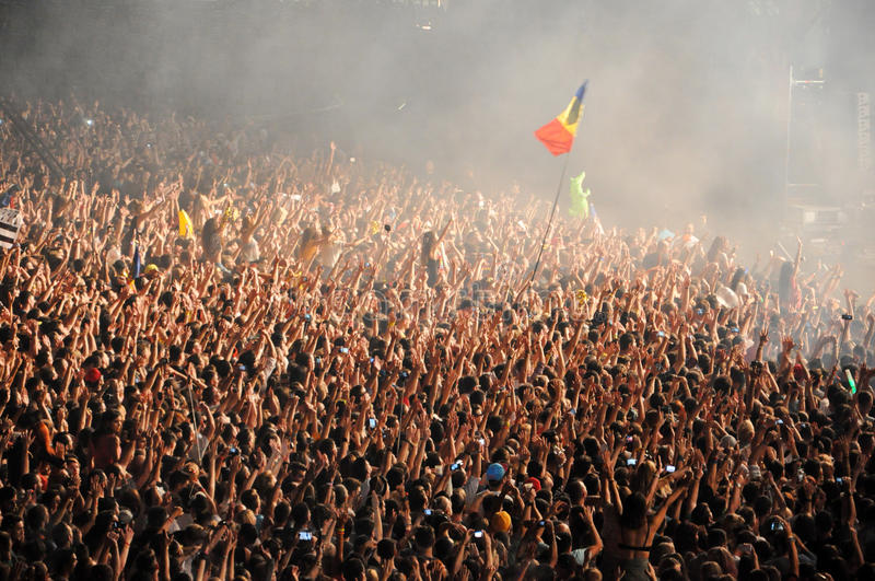 Party crowd dancing at concert. CLUJ NAPOCA, ROMANIA – AUGUST 2, 2015: Crowd of partying people enjoy a David Guetta live concert at the Untold Festival stock image