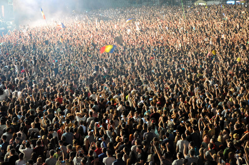Party crowd dancing at concert. CLUJ NAPOCA, ROMANIA – AUGUST 2, 2015: Crowd of partying people enjoy a David Guetta live concert at the Untold Festival royalty free stock image