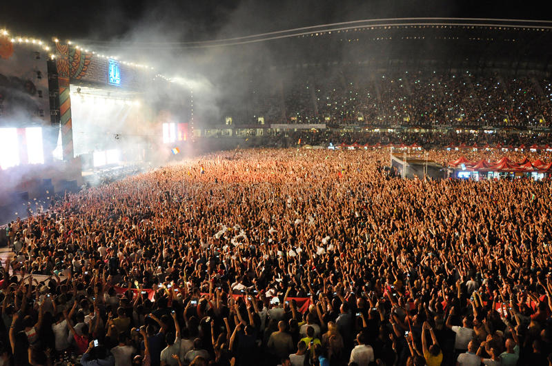 Party crowd dancing at concert. CLUJ NAPOCA, ROMANIA – AUGUST 2, 2015: Crowd of partying people enjoy a David Guetta live concert at the Untold Festival royalty free stock photos