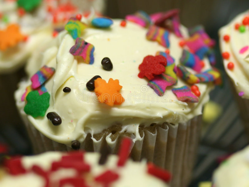 Party cupcakes macro. Macro of party cupcakes with sprinkles and butter cream frosting royalty free stock images