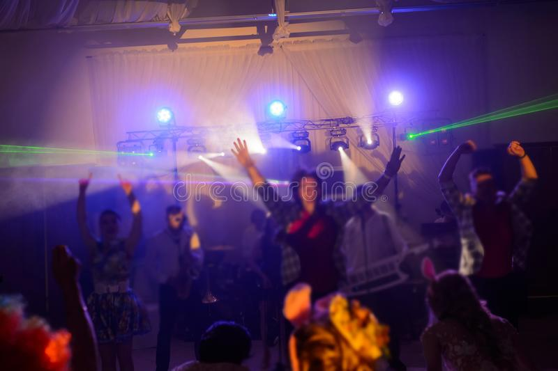The party, dancing on the floor. Colorful lights, hands up stock image