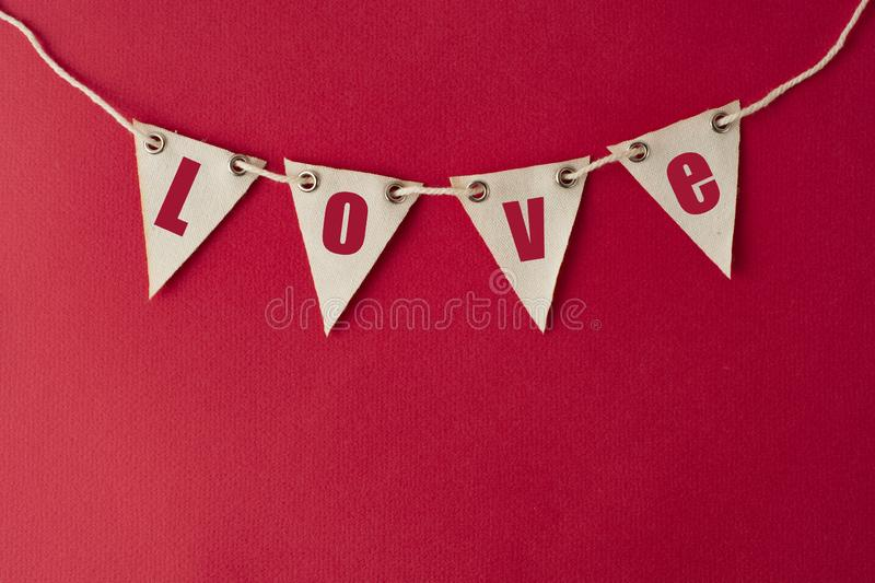 Valentine's day background. Party decorative garland with Love words, inscription. Red background for design or copy space. Party decorative garland with royalty free stock photo