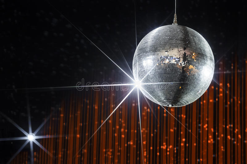 Party disco ball. Disco ball with stars in nightclub with striped orange and black walls lit by spotlight, party and nightlife entertainment industry royalty free stock photography