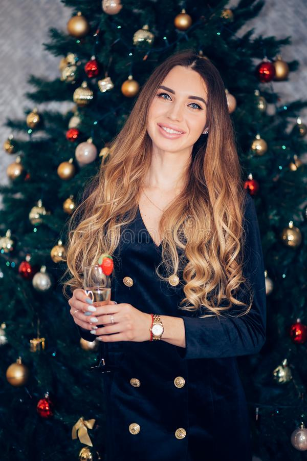 Party, drinks, holidays, celebration, smiling woman in evening dress with glass of champagnenear the tree royalty free stock photography